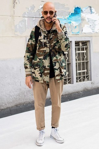 How to Wear Brown Sunglasses For Men: An olive camouflage field jacket and brown sunglasses are a good combo to keep in your casual styling collection. For shoes, you could stick to a more classic route with a pair of white canvas high top sneakers.