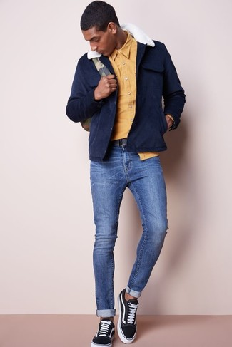 How to wear: navy suede field jacket, yellow long sleeve shirt, blue skinny jeans, black canvas low top sneakers