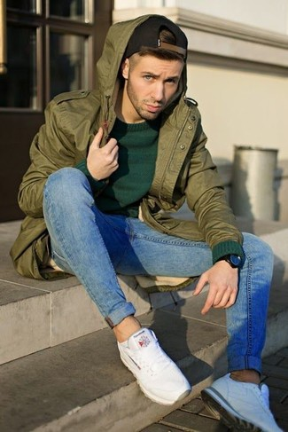 How to wear: olive fishtail parka, dark green crew-neck sweater, blue skinny jeans, white athletic shoes