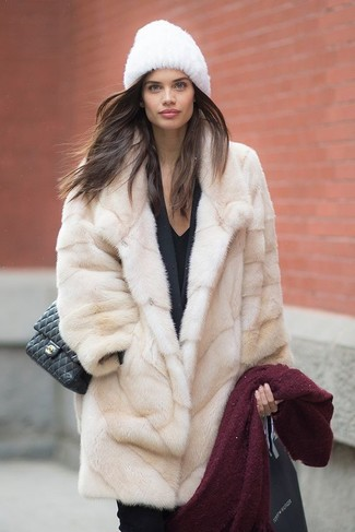 Go for a classic style in a beige fur coat and black fitted pants.