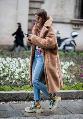 How to wear: tan fur coat, white and red print crew-neck t-shirt, light blue skinny jeans, multi colored athletic shoes