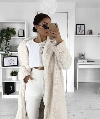 How to wear: white fur coat, white cropped sweater, white sweatpants, black sunglasses