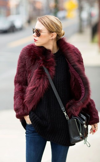 How to wear: burgundy fur coat, black knit oversized sweater, navy skinny jeans, black leather crossbody bag