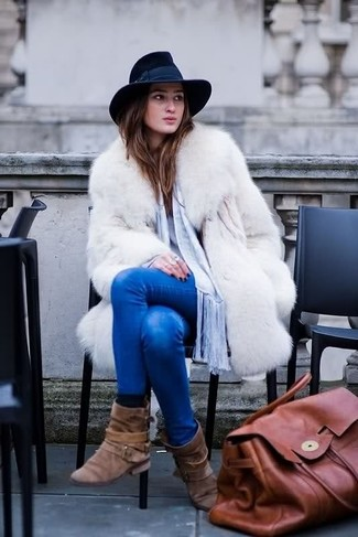 Wear a white fur coat and blue skinny jeans and you'll be the picture of elegance. Complement this look with brown suede mid-calf boots.