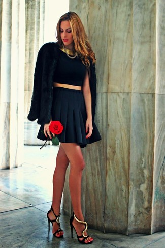 Consider teaming a black cropped top with a black pleated mini skirt for both chic and easy-to-wear look. This outfit is complemented perfectly with black and gold embellished satin heeled sandals.