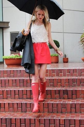 Cómo combinar: gabardina negra, blusa sin mangas de encaje blanca, minifalda roja, botas de lluvia rojas