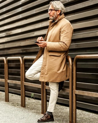 Cómo combinar: gabardina marrón claro, camisa de manga larga de cambray azul, vaqueros blancos, tenis de cuero en marrón oscuro
