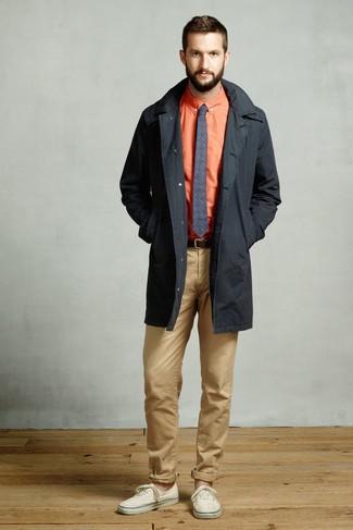 Cómo combinar: gabardina negra, camisa de vestir naranja, pantalón chino marrón claro, tenis de lona en beige