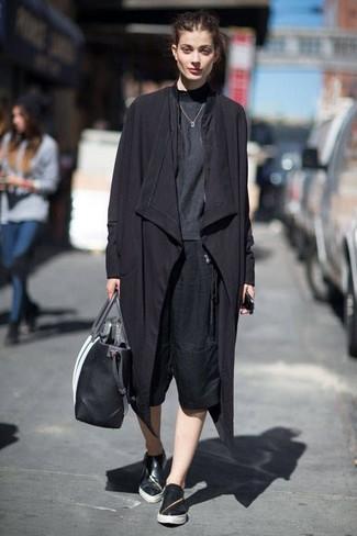 Cómo combinar: gabardina negra, camiseta de manga larga en gris oscuro, falda pantalón negra, zapatillas slip-on de cuero negras