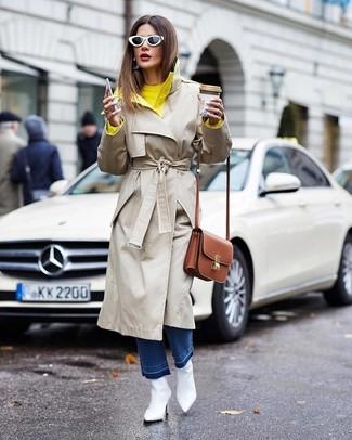 Cómo combinar: gabardina en beige, jersey con cuello circular amarillo, vaqueros azules, botines de cuero blancos