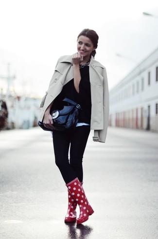Cómo combinar: gabardina en beige, jersey oversized negro, leggings negros, botas de lluvia a lunares rojas