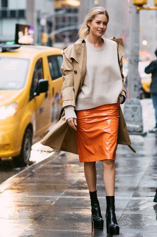 Cómo combinar: gabardina marrón claro, jersey con cuello circular blanco, falda lápiz de cuero naranja, botines de cuero negros