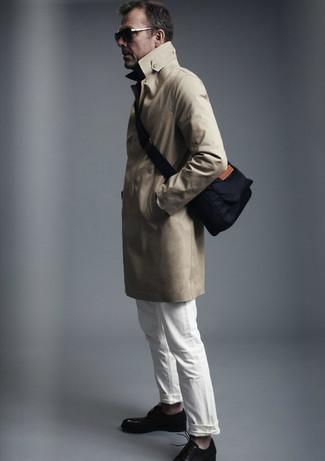 Cómo combinar: gabardina marrón claro, vaqueros blancos, zapatos derby de cuero negros, bolso mensajero de lona azul marino