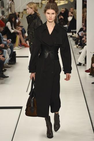 Cómo combinar: gabardina negra, botines de cuero en marrón oscuro, bolso deportivo de cuero en marrón oscuro, cinturón de cuero negro