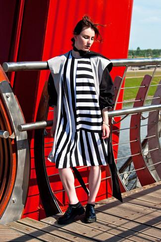 Cómo combinar: gabardina negra, vestido recto de rayas verticales en blanco y negro, zapatos oxford de cuero gruesos negros, bufanda de seda negra