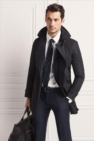Cómo combinar: gabardina negra, traje a cuadros azul marino, camisa de vestir blanca, bolsa de viaje de cuero negra