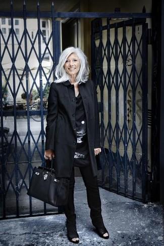 Cómo combinar: gabardina negra, túnica de seda estampada en negro y blanco, pantalones pitillo negros, botines de cuero con recorte negros