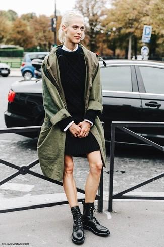 Cómo combinar: gabardina verde oliva, vestido jersey negro, camisa de vestir blanca, botas planas con cordones de cuero negras