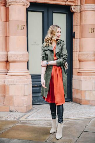 Cómo combinar: gabardina verde oliva, vestido midi de seda plisado naranja, leggings de cuero negros, botines de ante en beige