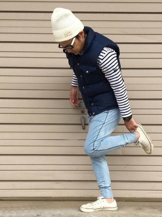 How to wear: navy quilted gilet, white and navy horizontal striped crew-neck sweater, light blue jeans, white low top sneakers