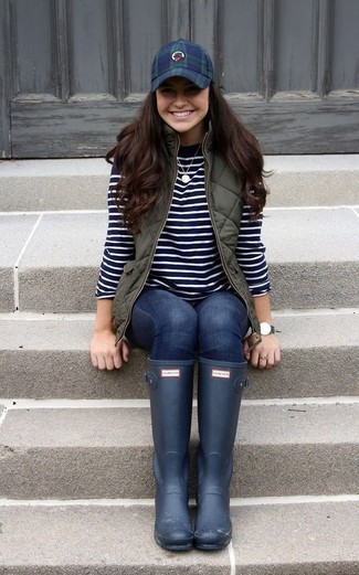 How to wear: olive quilted gilet, black and white horizontal striped crew-neck sweater, navy skinny jeans, navy rain boots