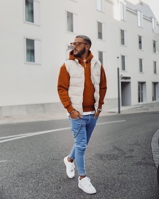 Blue Skinny Jeans Outfits For Men: Who said you can't make a fashionable statement with an off-duty look? You can do that easily in a beige quilted gilet and blue skinny jeans. On the fence about how to complement this ensemble? Wear a pair of white canvas low top sneakers to ramp it up.