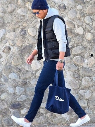 How to wear: black quilted gilet, grey hoodie, navy skinny jeans, white canvas slip-on sneakers