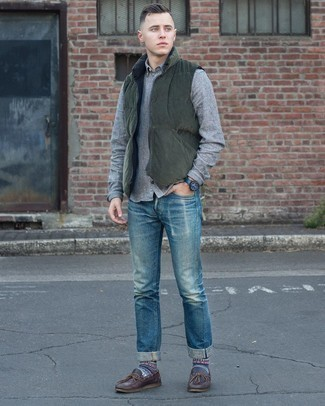 Blue Ripped Jeans Outfits For Men: This edgy combination of a dark green quilted gilet and blue ripped jeans couldn't possibly come across as anything other than incredibly stylish. If you wish to effortlessly elevate this outfit with footwear, add dark brown leather boat shoes to the equation.