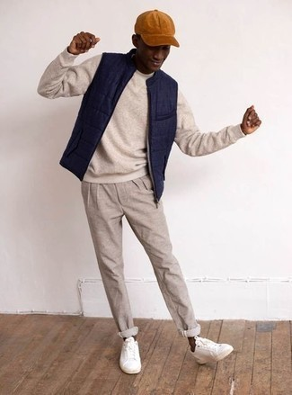 Baseball Cap Outfits For Men: A navy quilted gilet and a baseball cap are amazing menswear items to have in your current casual lineup. Tap into some David Beckham dapperness and elevate your ensemble with white canvas low top sneakers.