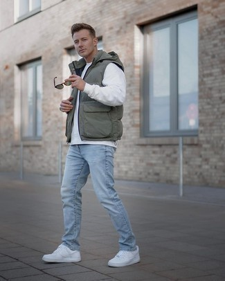 White and Red Leather Low Top Sneakers Outfits For Men: This edgy pairing of an olive gilet and light blue ripped jeans is very versatile and up for whatever the day throws at you. If you need to effortlessly class up this outfit with one single item, introduce a pair of white and red leather low top sneakers to this getup.