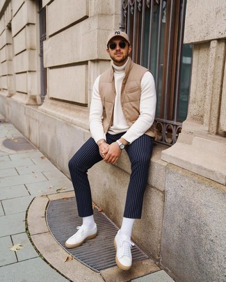 Baseball Cap Outfits For Men: Pairing a tan quilted gilet with a baseball cap is an on-point option for a relaxed look. Get a bit experimental on the shoe front and slip into a pair of white canvas low top sneakers.