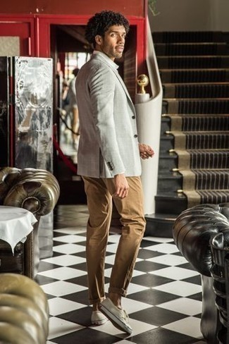 Grey Blazer Outfits For Men: This pairing of a grey blazer and khaki chinos is surely jaw-dropping, but it's very easy to wear too. White canvas low top sneakers are a surefire way to give a touch of stylish casualness to this ensemble.