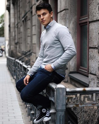 Men's Outfits 2021: If the situation permits casual dressing, you can rock a grey crew-neck sweater and navy jeans. Complement your ensemble with a pair of black and white canvas high top sneakers to make a standard ensemble feel suddenly edgier.