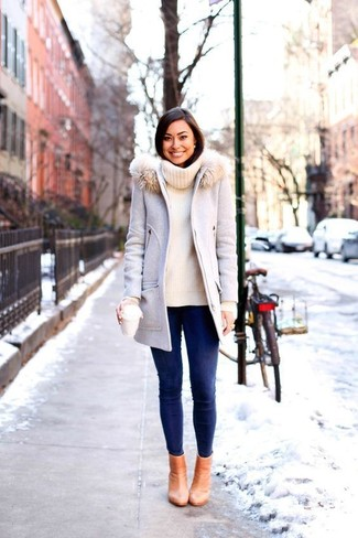 How to Wear a Grey Fur Collar Coat: This combo of a grey fur collar coat and navy skinny jeans delivers comfort and efficiency and helps you keep it low-key yet trendy. Tan leather ankle boots pull the look together.