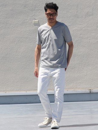 Grey Henley Shirt Outfits For Men: Beyond dapper and functional, this laid-back pairing of a grey henley shirt and white jeans will provide you with endless styling opportunities. Now all you need is a pair of beige canvas low top sneakers.