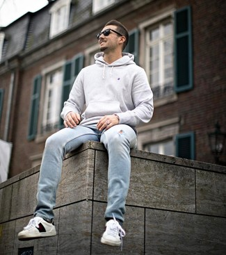 How to wear: grey hoodie, light blue ripped jeans, white print leather low top sneakers, black sunglasses