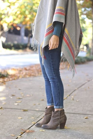 How to wear: grey horizontal striped poncho, blue skinny jeans, grey leather ankle boots