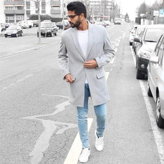 How to Wear a Grey Overcoat: Make a grey overcoat and light blue skinny jeans your outfit choice if you seek to look neat and relaxed without much effort. You can get a little creative on the shoe front and dial down your getup by finishing with a pair of white low top sneakers.