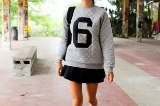 A grey print oversized sweater and a black pleated mini skirt is a wonderful combo to add to your casual lineup. This ensemble is our idea of perfection for when temps are dipping and fall is in full swing.