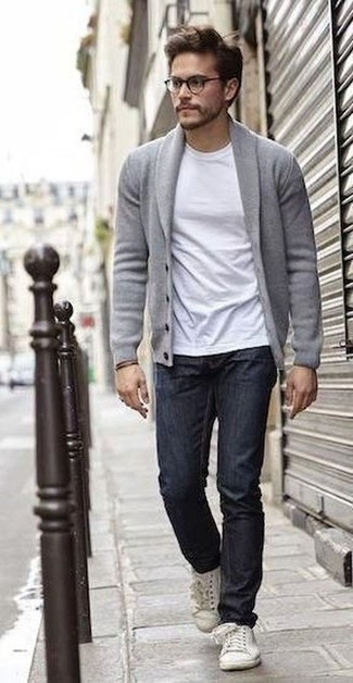 Men's Looks & Outfits: What To Wear In 2020: A grey shawl cardigan and navy jeans are the kind of a tested off-duty combo that you need when you have no time. Bump up this outfit with white leather low top sneakers.