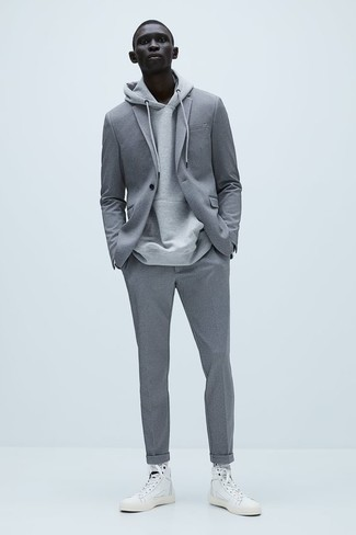How to Wear a Grey Hoodie For Men: For an outfit that's effortlessly neat and wow-worthy, rock a grey hoodie with a grey suit. Avoid looking too polished by rounding off with white canvas high top sneakers.