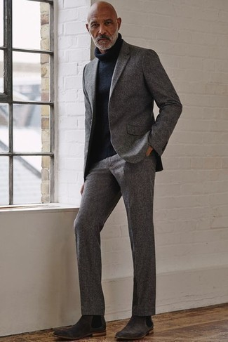 How to Wear a Grey Suit: Pairing a grey suit and a navy wool turtleneck is a fail-safe way to inject polish into your styling repertoire. Charcoal suede chelsea boots are a stylish addition to this look.