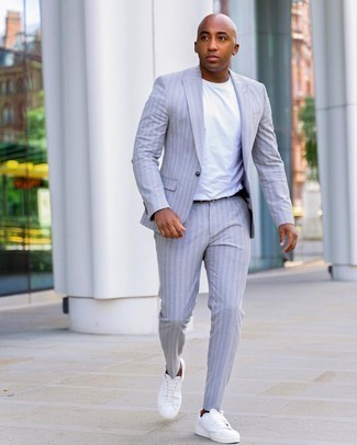 Men's Outfits 2020: For an effortlessly smart menswear style, opt for a grey vertical striped suit and a white crew-neck t-shirt — these items work beautifully together. For a more laid-back aesthetic, why not add a pair of white canvas low top sneakers to the equation?