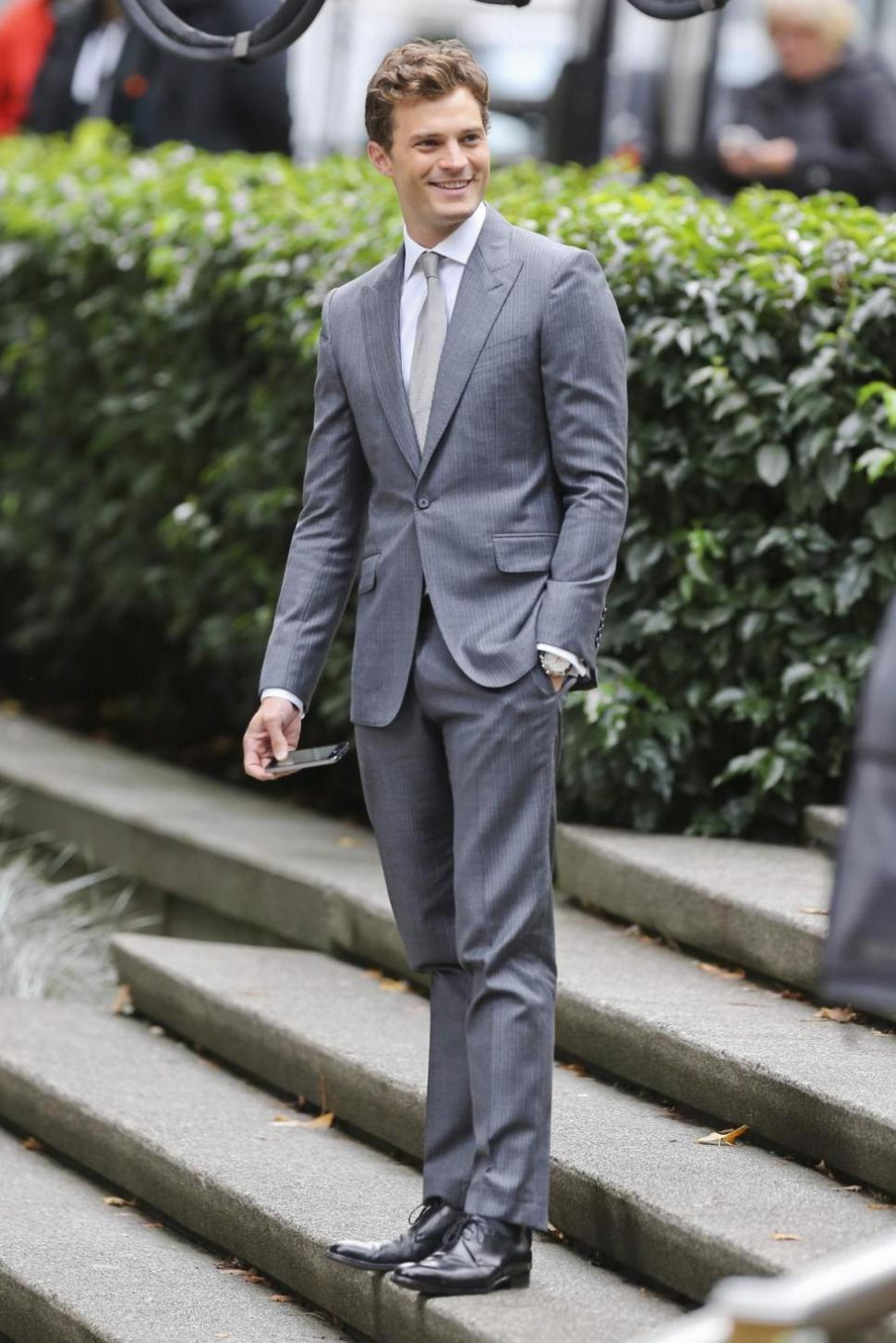 Jamie Dornan wearing Grey Suit, White Dress Shirt, Black Leather