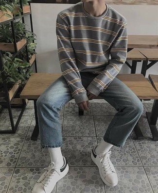 How to Wear White and Black Leather Low Top Sneakers For Men: A grey horizontal striped sweatshirt and light blue jeans make for the perfect foundation for a countless number of dapper outfits. A pair of white and black leather low top sneakers rounds off this look very nicely.