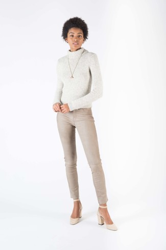 How to Wear Beige Skinny Jeans: This casual combination of a grey knit wool turtleneck and beige skinny jeans is extremely easy to put together in no time flat, helping you look amazing and ready for anything without spending a ton of time digging through your closet. Why not take a dressier approach with footwear and complete this look with beige suede pumps?