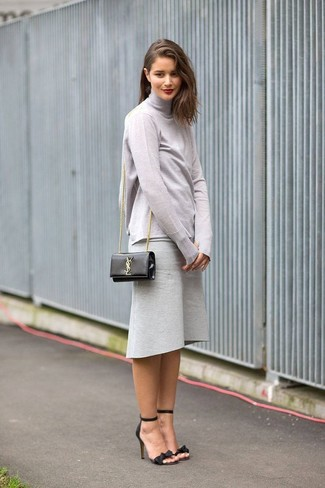 A smart casual pairing of a grey turtleneck and a grey wool midi skirt can maintain its relevance in many different circumstances. Balance this outfit with black and tan leather heeled sandals. On not so cold afternoons, you can wear a variation of this summer-to-fall getup and look absolutely amazing.