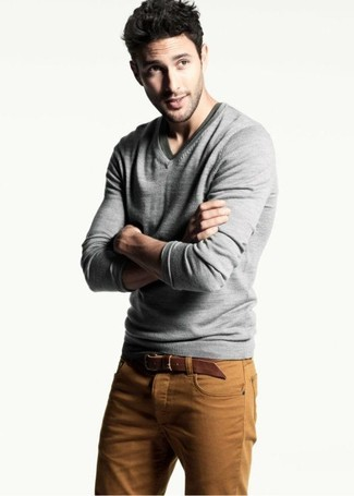 Pair a grey v-neck pullover with cognac jeans to create a great weekend-ready look.
