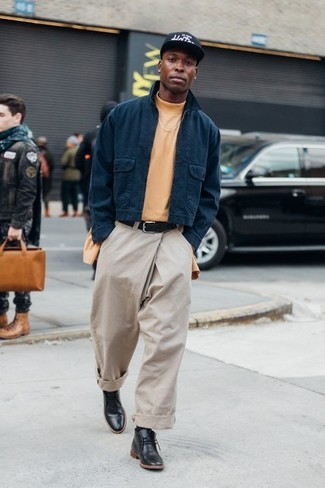 How to Wear an Orange Turtleneck For Men: This is definitive proof that an orange turtleneck and beige chinos look awesome when worn together in a laid-back outfit. Our favorite of a ton of ways to complete this look is with a pair of black leather desert boots.