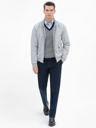 How to Wear a Grey V-neck Sweater For Men: This elegant pairing of a grey v-neck sweater and navy dress pants is a common choice among the dapper gentlemen. Dark brown leather loafers look right at home paired with this look.